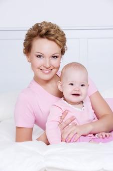 Портрет счастливой молодой attactive матери, лежа с ребенком на кровати дома