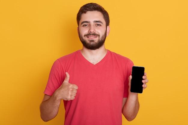 赤いカジュアルなtシャツを着てokのしぐさを見せて、空白の画面を持つ携帯電話を保持している幸せな若いひげを生やした流行に敏感な男の肖像