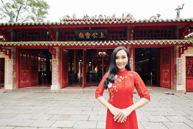 Портрет счастливой молодой красивой азиатской женщины в красном кружевном платье, стоящей у входа в храм