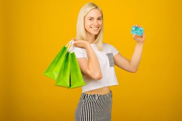 신용 카드를 들고 행복 한 젊은 아름 다운 금발 여자의 초상화