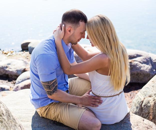 岩のビーチに座っている幸せな若い美しいカップルの肖像画