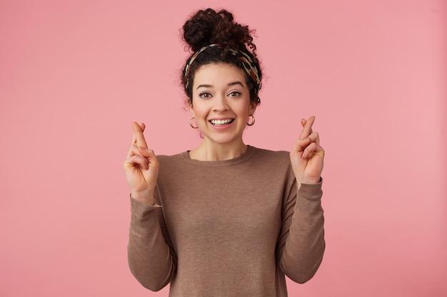 Портрет счастливой молодой красивой девушки с вьющимися темными волосами, скрещенными пальцами, надеется, что ей повезет, широко улыбается и смотрит в камеру, изолированную на розовом фоне.