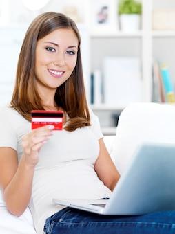 クレジットカードを保持しているとラップトップを使用して幸せな若い美しい女性の肖像画