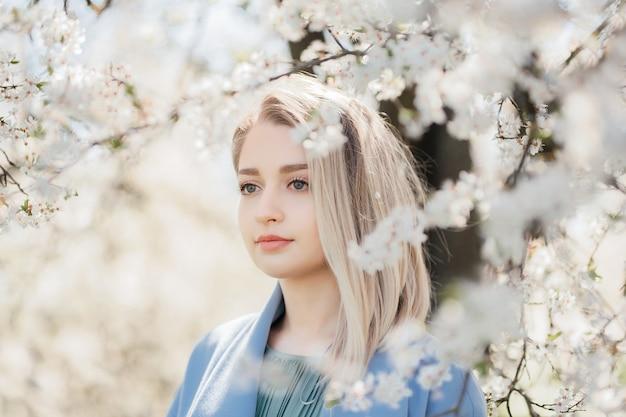 Портрет счастливой молодой блондинки в синей куртке, обнимающейся в белых цветах