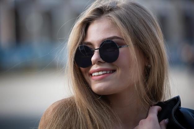 긴 머리를 가진 선글라스에 행복 한 젊은 금발 여자의 초상화