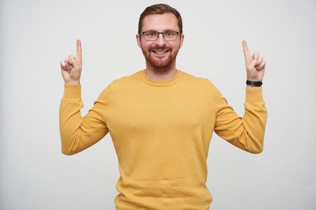 Портрет счастливого молодого бородатого брюнетки в очках, указывающего вверх с поднятыми указательными пальцами и широко улыбающегося, одетого в горчичный пуловер