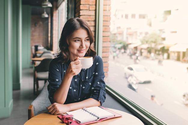 Портрет счастливой молодой деловой женщины с кружкой в руках, пьющей кофе утром в ресторане