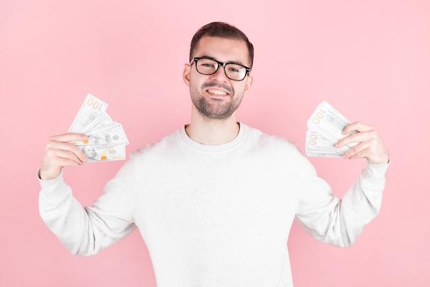분홍색 벽에 고립 된 돈 지폐를 들고 행복 한 젊은 사업가의 초상화