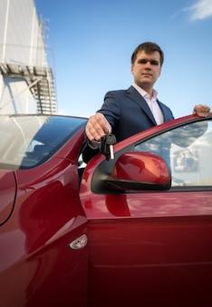 新しい車のキーを示す幸せな青年実業家の肖像画