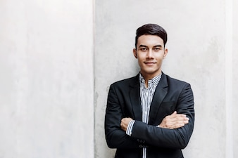Portrait of Happy Young Businessman standing at the Wall, Smiling and Crossed Arms