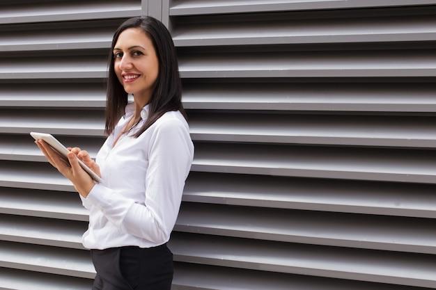 Портрет счастливой молодой коммерсантки используя цифровую таблетку