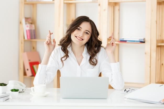 Портрет счастливой молодой кавказской деловой женщины, сидящей за офисным столом и держащей скрещенные пальцы