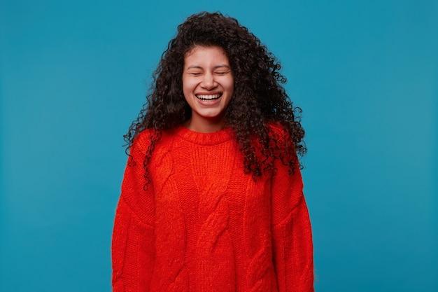 재미있는 농담에서 웃고있는 아름다운 검은 곱슬 머리를 가진 행복한 젊은 쾌활한 여자의 초상화