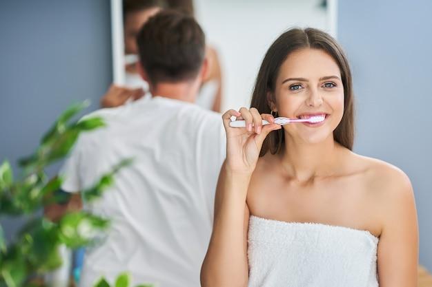 Портрет счастливой молодой пары, чистящей зубы в ванной комнате