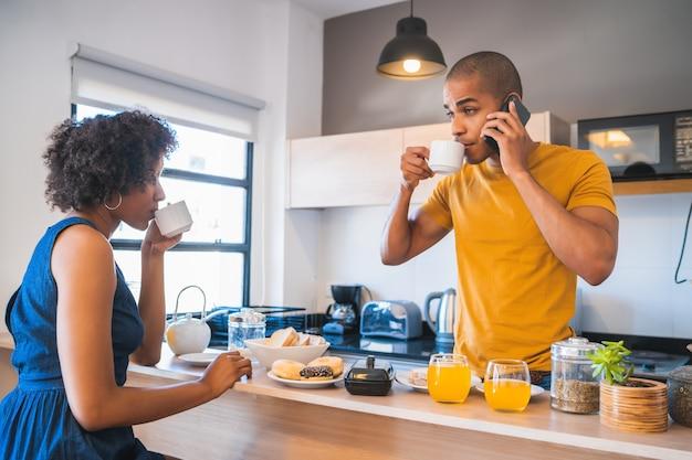 家で一緒に朝食を食べている幸せな若いカップルの肖像画。関係とライフスタイルの概念。
