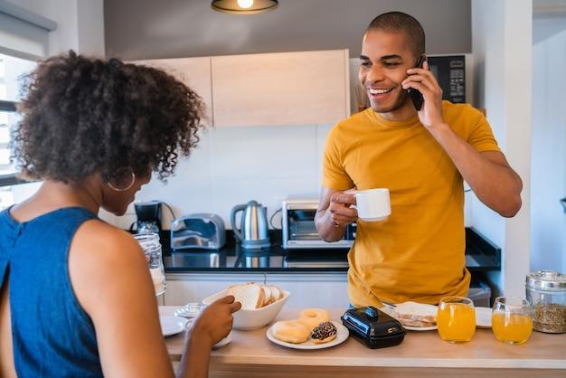 家で一緒に朝食を食べている幸せな若いカップルの肖像画