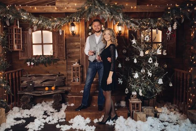 Портрет счастливой молодой пары в элегантных нарядах, улыбающейся лицом к лицу с двумя бокалами шампанского