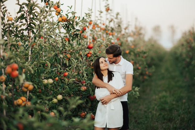 緑の屋外で熟した赤いリンゴの間で秋の果樹園で抱き締めて幸せな若いカップルの肖像画