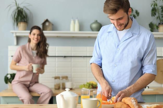 キッチンで一緒に料理し、家で朝にオレンジジュースを飲むパジャマで幸せな若いカップルの肖像画。