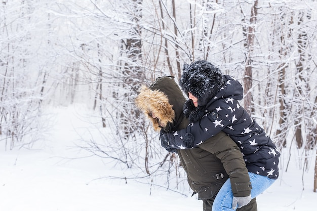 뒤에 그들의 친구와 함께 겨울 공원에서 행복 한 젊은 커플의 초상화.