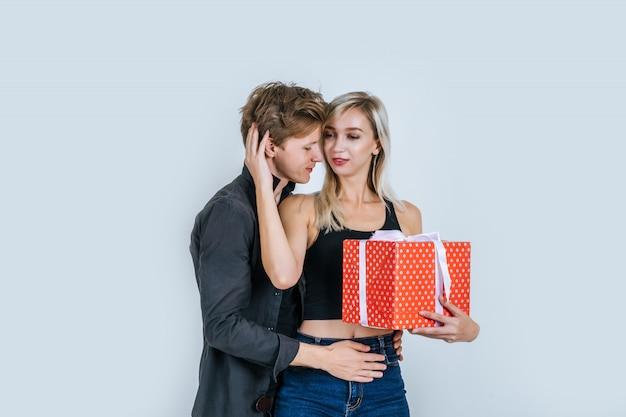 Портрет счастливой молодой пары любят вместе сюрприз с подарочной коробке