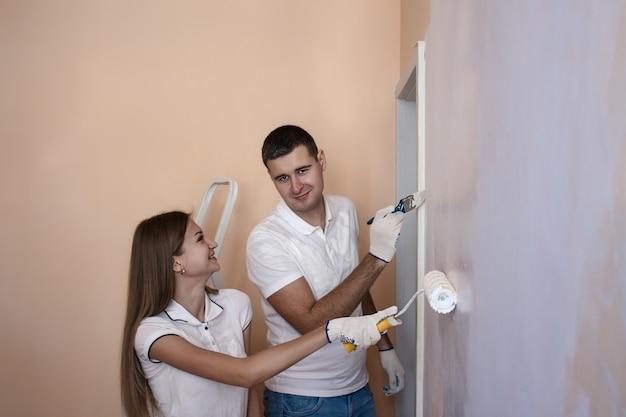 Портрет счастливой молодой пары, расписывающей внутреннюю стену нового дома или квартиры. девушка улыбается.