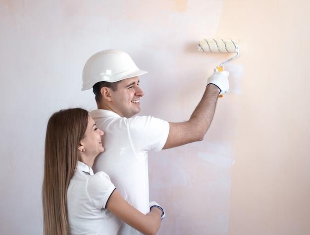Портрет счастливой молодой пары, рисующей интерьерную стену нового дома или квартиры, она обнимает его