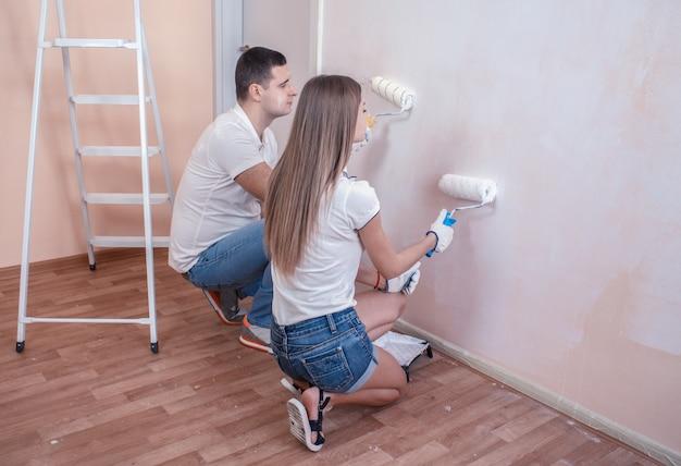 Портрет счастливой молодой пары, расписывающей внутреннюю стену нового дома или квартиры