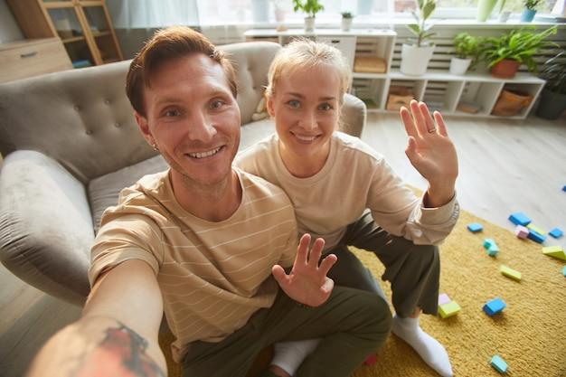 笑顔と部屋に座って手を振って幸せな若いカップルの肖像画