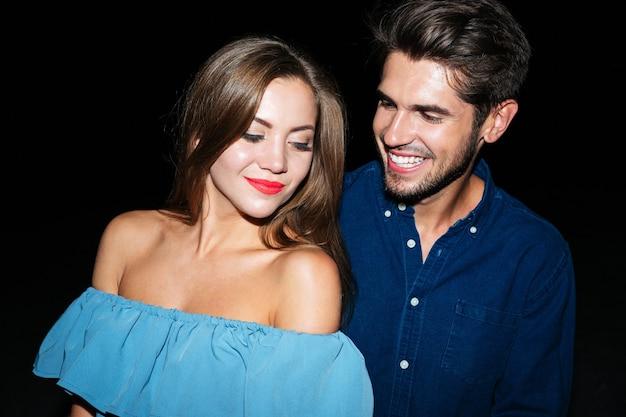 Портрет счастливой молодой пары, стоя вместе ночью
