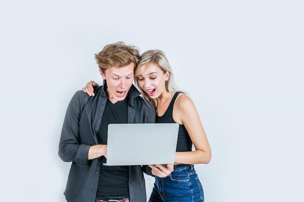 Портрет счастливой молодой пары с помощью портативного компьютера