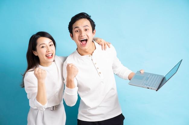 파란 벽에 노트북을 사용 하여 행복 한 젊은 커플의 초상화