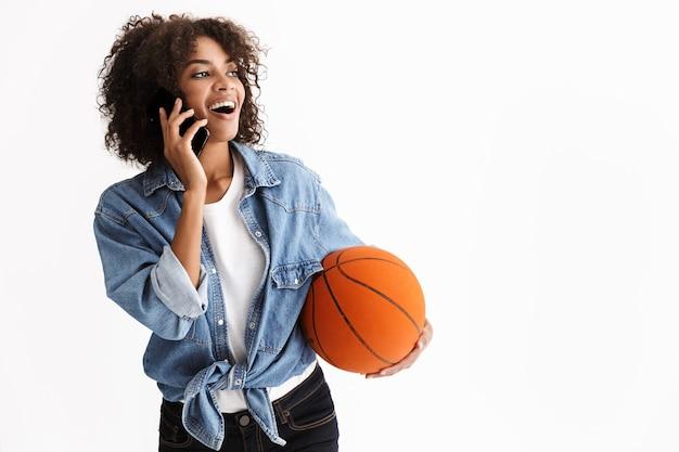 Портрет счастливой молодой взволнованной спортивной женщины-африканца, держащей баскетбол, позирует изолированной над белой стеной, разговаривает по мобильному телефону