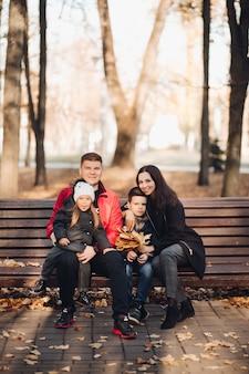 秋の公園で休んでいる子供たちと幸せな若い家族の肖像画。親子関係の概念
