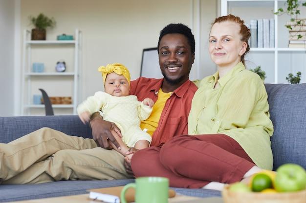 自宅のソファに座ってカメラに笑顔の新生児と幸せな若い家族の肖像画
