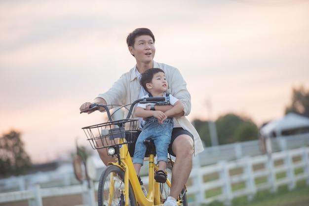 自転車に乗った幸せな若い父と息子のポートレート。夕暮れ時に公園で遊んでいる父と息子。フィールドで楽しむ人々。フレンドリーな家族と夏休みのコンセプト。