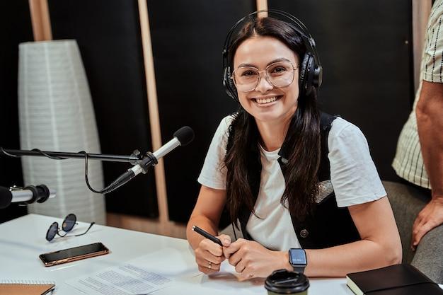 스튜디오에서 방송하는 동안 카메라를 보며 웃고 있는 행복한 젊은 여성 라디오 진행자의 초상화