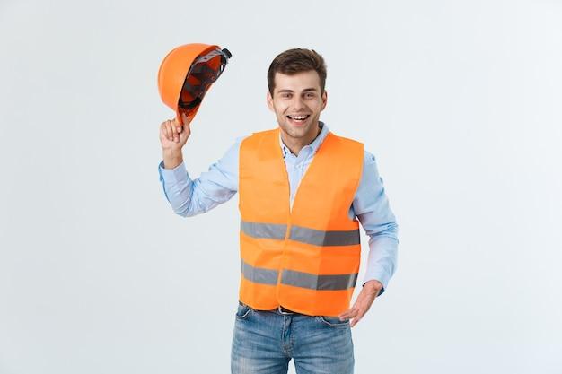 白い背景の上に分離されたオレンジ色のベストと幸せな若い職長の肖像画。