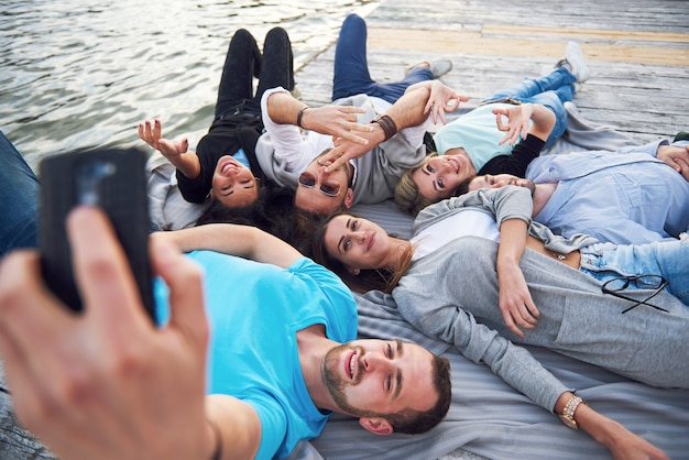 Портрет счастливых молодых друзей на пристани у озера. наслаждаясь днем и делая селфи.