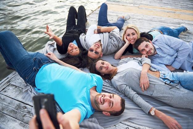湖の桟橋で幸せな若い友人の肖像画。その日を楽しみながら自撮りをしながら。