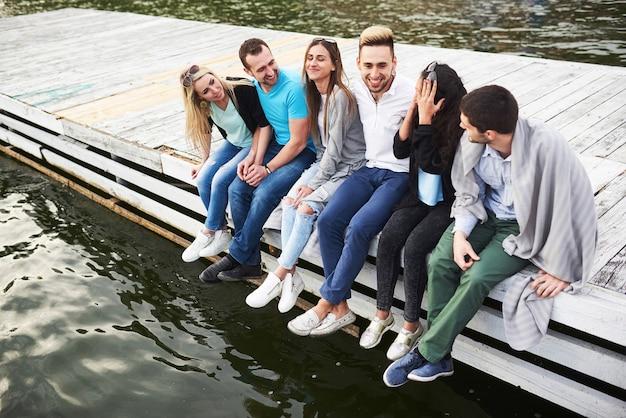Портрет счастливых молодых друзей, сидящих на пристани у озера.