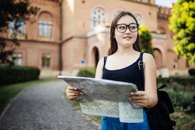 Портрет счастливой молодой девушки приносят рюкзак в поисках чего-то и держат карту путешествия в неизвестном городе
