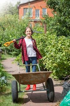晴れた日に庭で手押し車とシャベルでポーズをとって幸せな少女の肖像画