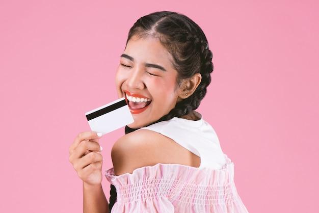 ピンクの背景にクレジットカードを表示する幸せな若い女の子の肖像