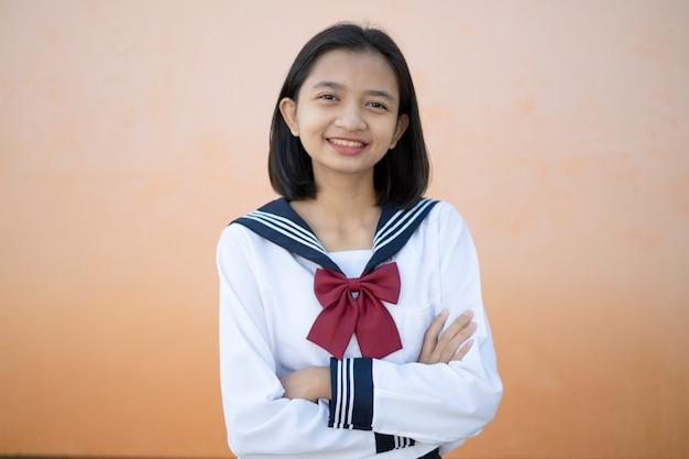 肖像画の幸せな少女は学校で制服を着ています