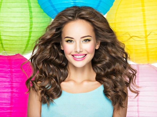 긴 갈색 머리를 가진 행복 한 젊은 여자의 초상화. 흰색 배경 위에 백인 꽤 웃는 여자의 근접 촬영 얼굴