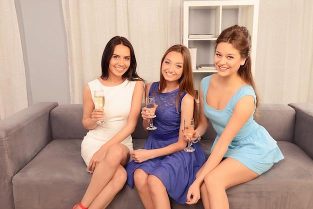 シャンパンで祝う幸せな若いガールフレンドの肖像画
