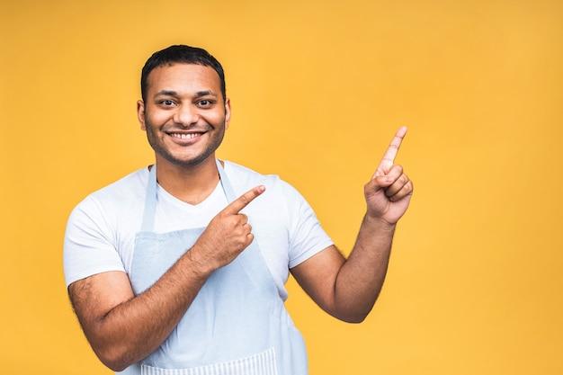 幸せな若いハンサムなアフリカ系アメリカ人のインド料理人またはシェフの笑顔で、指で脇を指して、黄色の背景の上に分離された興奮した表情での肖像画。