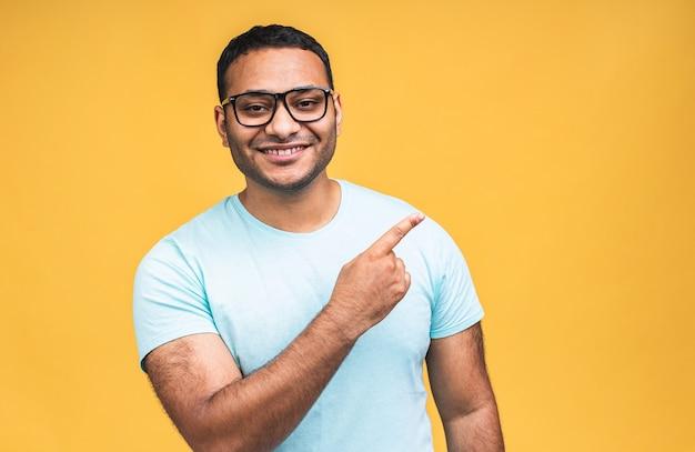 黄色の背景の上に分離された興奮した顔の表情で、カジュアルな笑顔で、指で脇を指して、幸せな若いハンサムなアフロアメリカのインド人男性の肖像画。