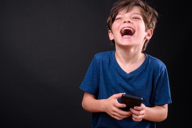 電話を使用しながら笑っている幸せな若いハンサムな男の子の肖像画